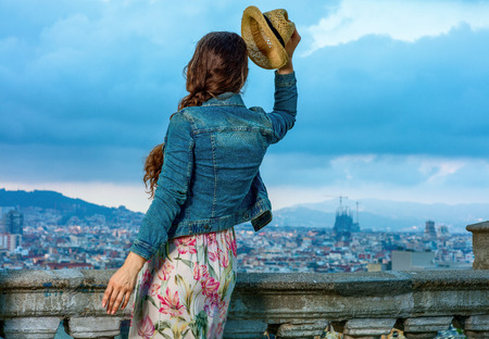 Perfect evening with stunning view. Seen from behind stylish tourist woman in long dress and straw hat in the front of cityscape of Barcelona, Spain having fun time Stock Photo