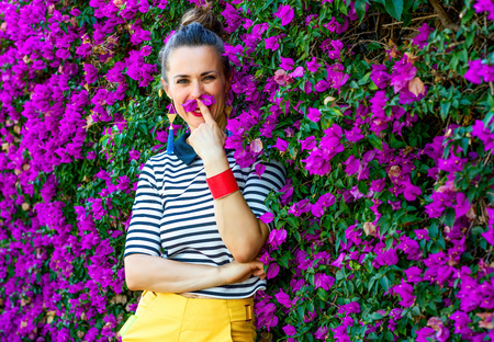 Colorful Freshness. smiling trendy woman in yellow shorts and stripy shirt in the front of colorful magenta flowers bed having fun time Stock Photo