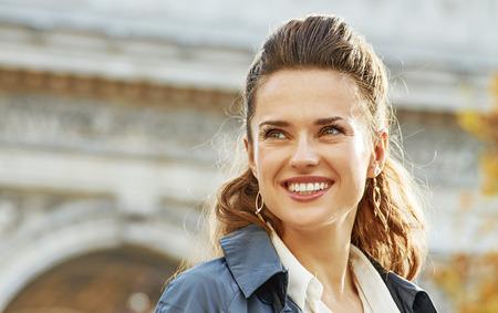 파리의 세련된 가을. 프랑스 파리에서에서 트렌치 코트에 행복 젊은 유행 여자 제쳐두고 찾고 스톡 콘텐츠