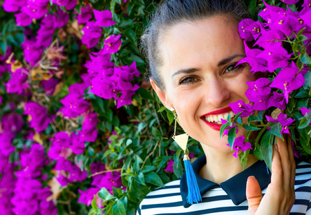 Colorful Freshness. happy stylish woman in stripy shirt against colorful magenta flowers bed