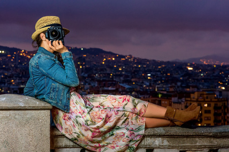 Perfect evening with stunning view. modern tourist woman in long dress and straw hat in Barcelona, Spain with digital camera sitting on the parapet and taking photo