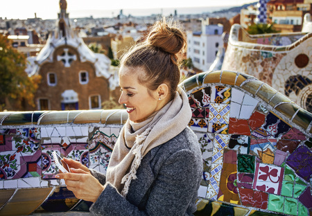 Barcelona signature style. smiling elegant traveller woman in coat at Guell Park in Barcelona, Spain writing sms Banque d'images