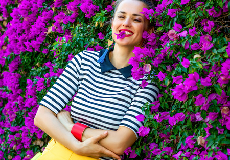 Colorful Freshness. Portrait of relaxed stylish woman in yellow shorts and stripy shirt in the front of colorful magenta flowers bed Stock Photo