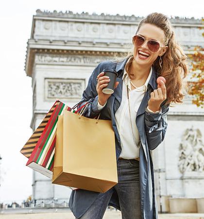 パリのスタイリッシュな秋。コーヒーとマカロンを持つフランス、パリのアーク・ド・トリオンフの近くに買い物袋を持つサングラスをかけた笑顔 写真素材