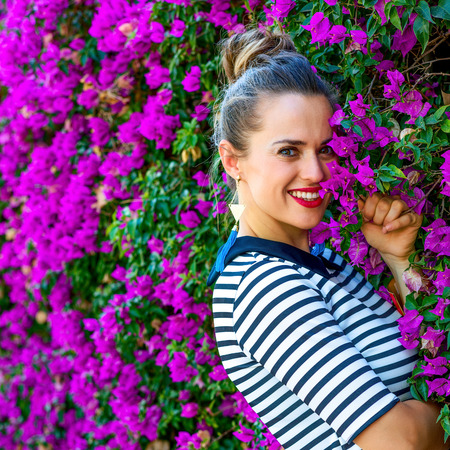 Colorful Freshness. Portrait of smiling stylish woman in yellow shorts and stripy shirt near colorful magenta flowers bed Stockfoto