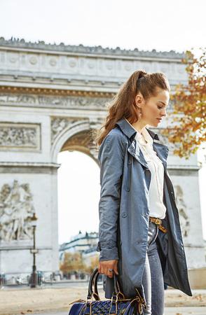 파리의 세련된 가을. 파리, 프랑스의 개선문 근처 트렌치 코트에 잠겨있는 현대 여자 스톡 콘텐츠