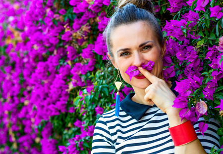 Colorful Freshness. Portrait of smiling stylish woman in stripy shirt near colorful magenta flowers bed having fun time