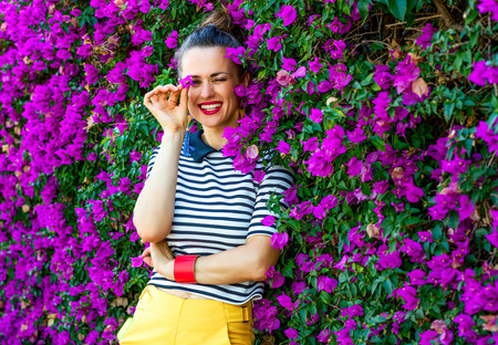 Colorful Freshness. happy stylish woman in yellow shorts and stripy shirt near colorful magenta flowers bed having fun time Stock Photo