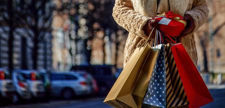 Herontdek dingen waar iedereen van houdt in Milaan. elegante toeristische vrouw met boodschappentassen en kerstcadeau in de buurt van Sforza Castle in Milaan, Italië op zoek opzij Stockfoto
