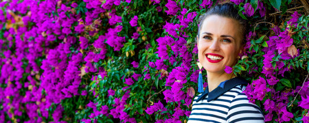 Colorful Freshness. Portrait of relaxed young woman in  stripy shirt in the front of colorful magenta flowers bed Stock Photo