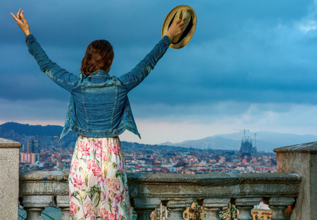 Perfect evening with stunning view. Seen from behind elegant tourist woman in long dress and straw hat in the front of city panorama of Barcelona, Spain rejoicing