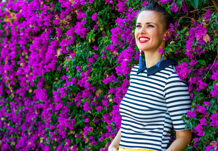 Colorful Freshness. relaxed trendy woman in stripy shirt near colorful magenta flowers bed looking into the distance