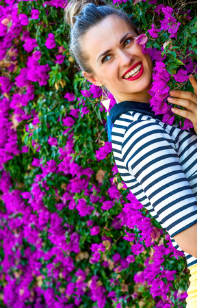 Colorful Freshness. happy trendy woman in yellow shorts and stripy shirt against colorful magenta flowers bed looking aside