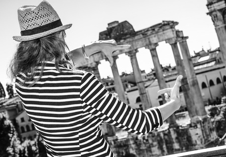 Roman Holiday. Seen from behind trendy tourist woman in the front of Roman Forum in Rome, Italy framing with hands