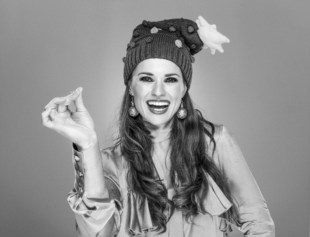 Stunning season. smiling young woman in funny Christmas hat isolated on grey snapping with fingers