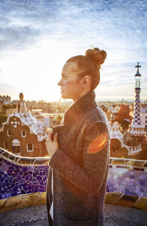 Barcelona signature style. modern tourist woman in coat at Guell Park in Barcelona, Spain looking into the distance 版權商用圖片