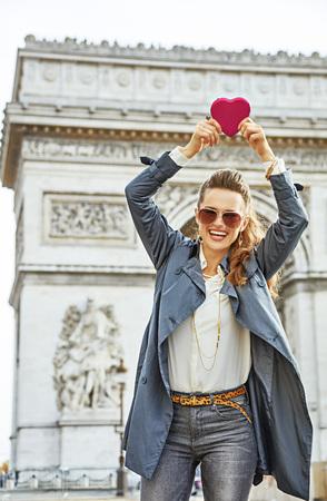 파리의 세련된 발렌타인 데이. 파리, 프랑스 붉은 마음을 보여주는 프랑스 파리에서에서 트렌치 코트에 웃 고 유행 젊은 여자의 초상화 모양의 초콜렛