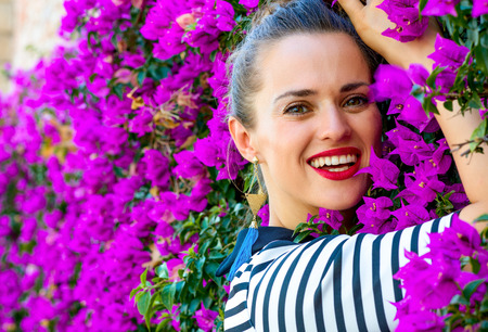 Colorful Freshness. Portrait of smiling stylish woman in stripy shirt against colorful magenta flowers bed Stock Photo
