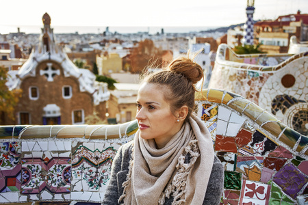 Barcelona signature style. elegant woman in coat in Barcelona, Spain looking into the distance while sitting on bench
