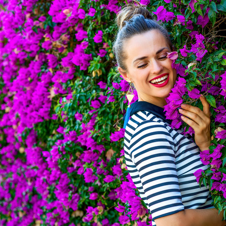 Colorful Freshness. Portrait of relaxed young woman in yellow shorts and stripy shirt near colorful magenta flowers bed