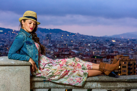 Perfect evening with stunning view. modern traveller woman in long dress and straw hat against cityscape of Barcelona, Spain sitting on the parapet Stock fotó