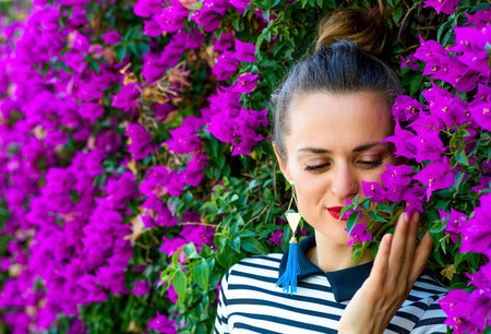 Colorful Freshness. smiling trendy woman in stripy shirt enjoying colorful magenta flowers Stock Photo