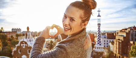 Barcelona signature style. smiling elegant tourist woman in coat in Barcelona, Spain showing heart shaped hands Stock Photo