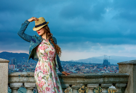 Perfect evening with stunning view. stylish traveller woman in long dress and straw hat against city panorama of Barcelona, Spain posing Stock Photo