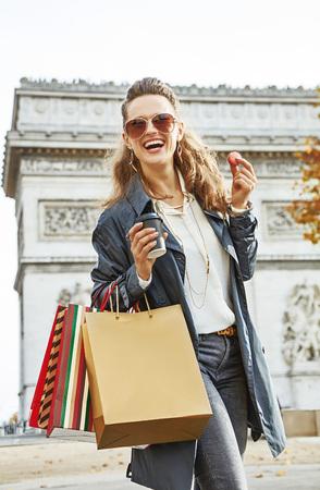 パリのスタイリッシュな秋。コーヒーとマカロンを持つパリ、フランスのショッピングバッグとサングラスで笑顔トレンディな女性