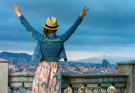 Perfect evening with stunning view. Seen from behind elegant traveller woman in long dress and straw hat in the front of cityscape of Barcelona, Spain rejoicing
