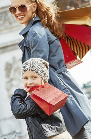 Stylish autumn in Paris. smiling young mother and child with shopping bags near Arc de Triomphe in Paris, France walking
