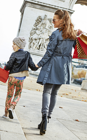 Stylish autumn in Paris.  Seen from behind full  length portrait of happy young mother and child with shopping bags in Paris, France looking aside and walking