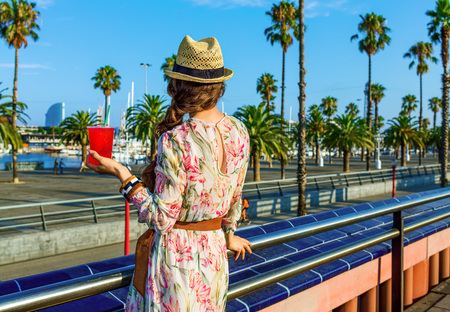 Summertime at colorful Barcelona. Seen from behind young woman in long dress and straw hat on embankment in Barcelona, Spain with bright red beverage looking into the distance Stock Photo