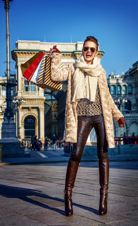 Rediscovering things everybody love in Milan. Full length portrait of smiling modern woman in fur coat and sunglasses at Piazza del Duomo in Milan, Italy rejoicing Stock Photo
