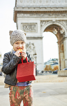 Stylish autumn in Paris. happy modern child with red present bag near Arc de Triomphe in Paris eating French macaroon
