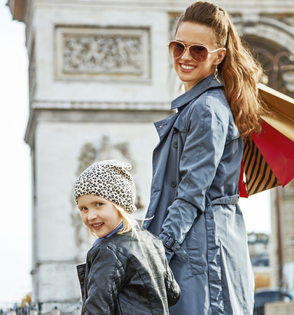Stylish autumn in Paris. happy trendy mother and child with shopping bags in Paris, France