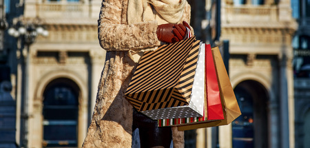 Rediscovering things everybody love in Milan. smiling young traveller woman with shopping bags near Galleria Vittorio Emanuele II in Milan, Italy looking into the distance Stock Photo