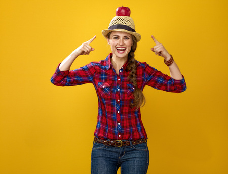Healthy food to your table. Portrait of happy young woman grower in checkered shirt isolated on yellow pointing on apple on head