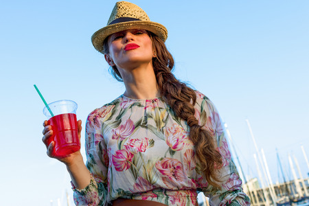 Summertime at colorful Barcelona. trendy tourist woman in long dress and straw hat in Barcelona, Spain with bright red beverage having fun time Stock Photo