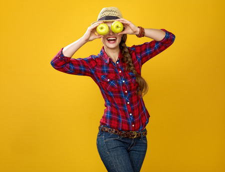 Healthy food to your table. Portrait of happy modern woman farmer in checkered shirt isolated on yellow background holding apples in the front of face like big eyes