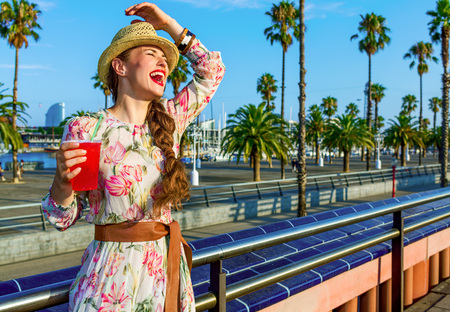 Summertime at colorful Barcelona. happy young woman in long dress and straw hat in Barcelona, Spain with bright red beverage having fun time