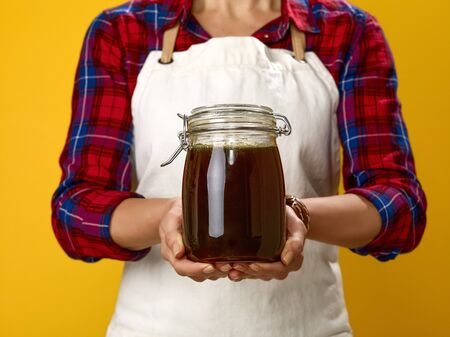 Healthy food to your table. Closeup on modern woman cook wearing apron isolated on yellow showing jar with honey