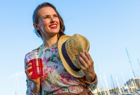 Summertime at colorful Barcelona. happy elegant traveller woman in long dress and straw hat on embankment in Barcelona, Spain with bright red beverage looking into the distance 版權商用圖片
