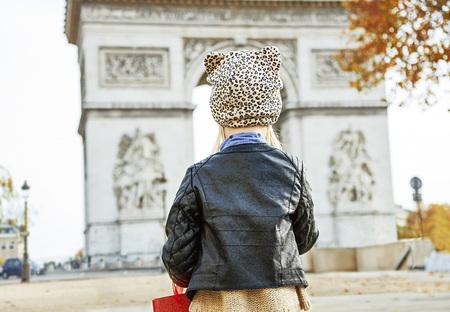 Stylish autumn in Paris. Seen from behind modern child in Paris, France