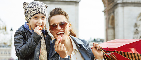 Stylish autumn in Paris. Portrait of smiling modern mother and daughter with shopping bags near Arc de Triomphe in Paris, France eating macaroons