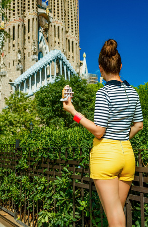 Barcelona - July, 10, 2017: Seen from behind young woman in yellow shorts and stripy shirt near Sagrada Familia in Barcelona, Spain with waffle