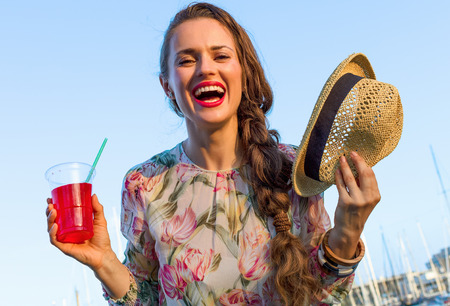 Summertime at colorful Barcelona. happy young traveller woman in long dress and straw hat in Barcelona, Spain with bright red beverage Stock Photo