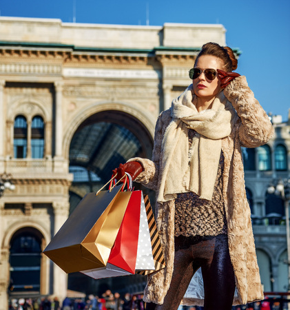 Rediscovering things everybody love in Milan. elegant woman in fur coat and sunglasses near Galleria Vittorio Emanuele II in Milan, Italy looking into the distance Stock Photo