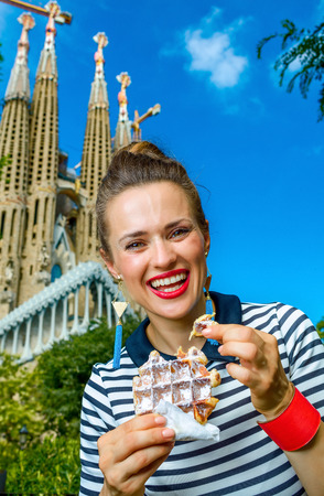 Barcelona - July, 10, 2017: Portrait of trendy woman in stripy shirt in the front of Sagrada Familia in Barcelona, Spain eating waffle Editorial