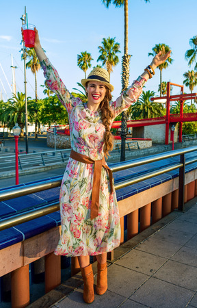 Summertime at colorful Barcelona. happy stylish tourist woman in long dress and straw hat on embankment in Barcelona, Spain with bright red beverage rejoicing